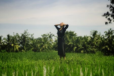 outdoors yoga and meditation at rice field - attractive and happy middle aged Asian Korean woman enjoying yoga and relaxation in connection with the nature in healthy lifestyle and wellness