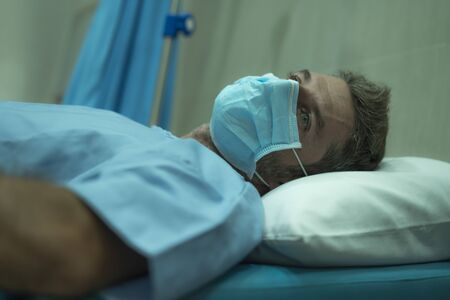 attractive and scared man infected by covid-19 - dramatic portrait of adult male in face mask receiving treatment at hospital suffering respiratory disease lying on bed worried