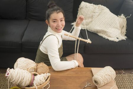 Asian girl enjoying macrame handcraft hobby - young happy and pretty Chinese at home doing macramŽ using ropes, cords and threads in domestic handmade decoration