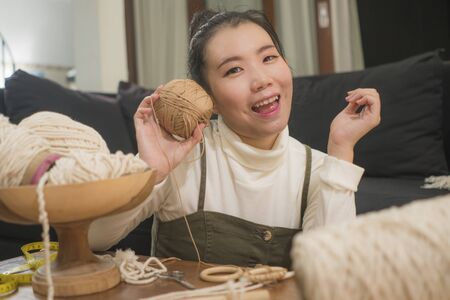 Asian girl enjoying macrame handcraft hobby - young happy and pretty Japanese at home doing macramŽ using ropes, cords and threads in domestic handmade decoration