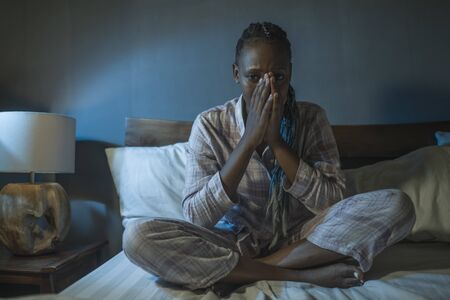 young sad and depressed black African American woman sitting on bed at home sleepless and worried at night feeling overwhelmed suffering depression problem and insomnia Reklamní fotografie
