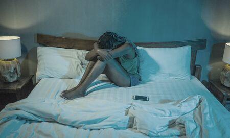 dramatische levensstijl portret van jonge trieste en depressieve zwarte Afro-Amerikaanse vrouw huilend in bed met mobiele telefoon slachtoffer van cyberpesten of gebroken hart in haar slaapkamer Stockfoto