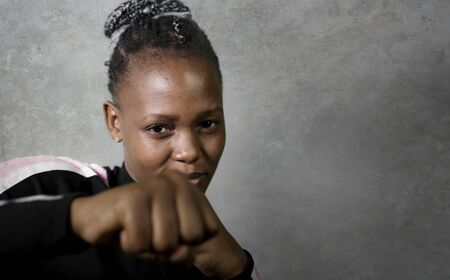 isolated portrait of young cool and confident black afro woman in fighting stance looking defiant rising her fist throwing punch in badass attitude isolated on grunge background