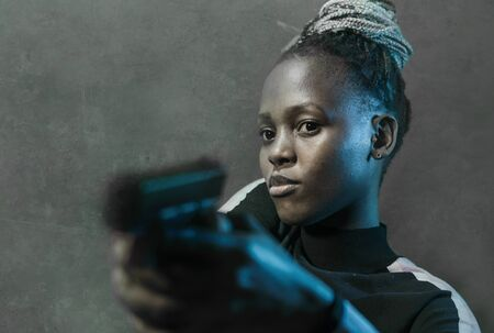Hollywood movie style portrait of young attractive and confident black afro  woman holding gun as special federal agent or mobster pointing the handgun