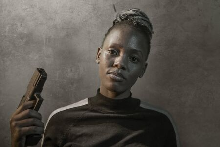 Hollywood movie style portrait of young attractive and confident black African woman holding gun as special federal agent or mobster pointing the handgun