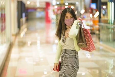 New normal habits - young attractive and happy Asian Korean woman at shopping mall happy and excited enjoying sale in beauty fashion store carrying shopping bags Archivio Fotografico