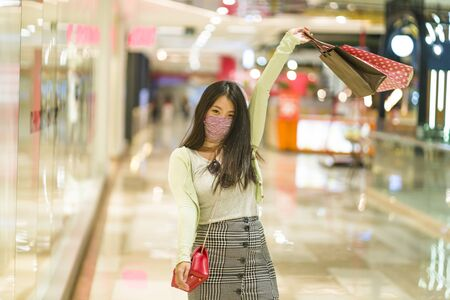 New normal habits - young attractive and happy Asian Korean woman at shopping mall happy and excited enjoying sale in beauty fashion store carrying shopping bags