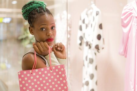 young happy and beautiful African American girl at buying shopping mall - lifestyle portrait of millennial black girl enjoying looking clothing at beauty fashion store playful and excited