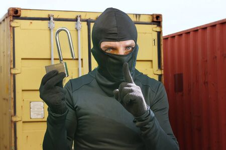 thief at work - criminal man in black covered with balaclava mask holding unlocked padlock at shipping area break in storage containers in robbery and crime concept