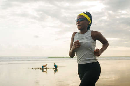 young attractive black girl post quarantine jogging - new normal running workout of athletic and fit afro American woman at beautiful beach wearing face mask