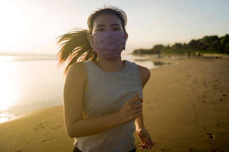 new normal running workout of Asian girl in face mask - young happy and attractive Korean woman jogging on the beach in post quarantine outdoors exercise on beautiful sunset Imagens