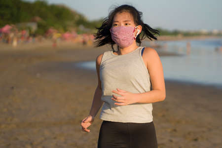 new normal running workout of Asian girl in face mask - young happy and beautiful Korean woman jogging on the beach in post quarantine outdoors exercise