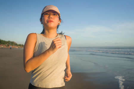 Asian girl running on the beach - young attractive and happy Korean woman doing jogging workout at beautiful beach enjoying fitness and healthy runner lifestyle