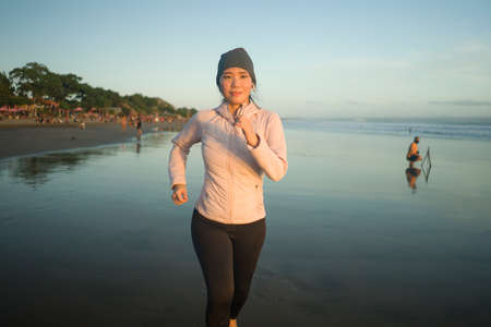 Asian girl running on the beach - young attractive and happy  woman doing jogging workout at beautiful beach enjoying fitness and healthy runner lifestyle