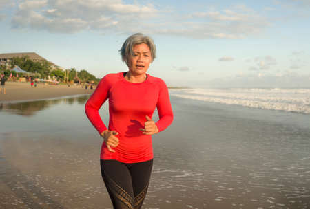 fit and attractive middle aged woman running on the beach - 40s or 50s mature lady with grey hair doing hard jogging workout enjoying fitness and healthy lifestyle at beautiful sea landscape