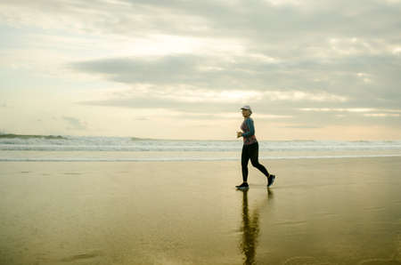 Silhouette of middle aged woman running on the beach - 40s or 50s attractive mature lady doing jogging workout enjoying fitness and healthy lifestyle at beautiful sea sunset landscape Imagens