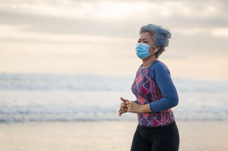 new normal running workout with face mask - attractive and happy middle aged woman on her 40s or 50s doing post quarantine jogging at beautiful beach in healthy lifestyle concept Imagens