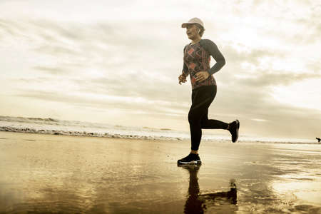 Silhouette of middle aged woman running on the beach - 40s or 50s attractive mature lady doing jogging workout enjoying fitness and healthy lifestyle at beautiful sea sunset landscape 写真素材