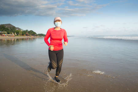 new normal running workout with face mask - attractive and happy middle aged woman on her 40s or 50s doing post quarantine jogging at beautiful beach in healthy lifestyle concept 写真素材