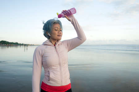 happy tired and thirsty middle aged woman drinking and pouring water on her head refreshing after beach running workout - 40s or 50s attractive mature lady exhausted after jogging