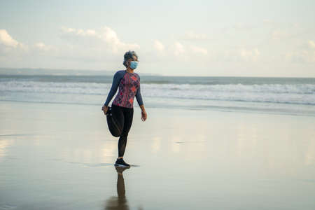 mature lady in face mask stretching before new normal running workout - attractive and happy middle aged woman stretching legs before quarantine beach jogging post quarantine Imagens