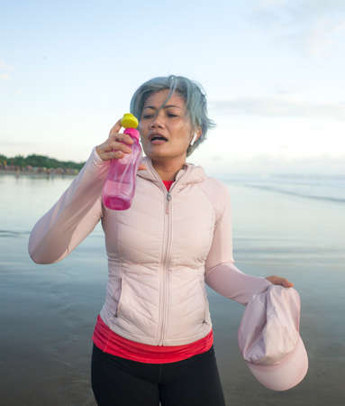 happy tired and thirsty middle aged woman drinking water after beach running workout - 40s or 50s attractive mature lady with grey hair re hydrating  exhausted after jogging