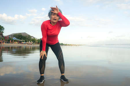 lifestyle portrait of fit and tired middle aged woman after beach running workout - 40s or 50s attractive mature lady with grey hair breathing exhausted after jogging