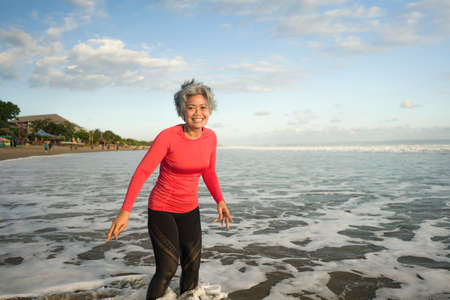 lifestyle portrait of fit and happy middle aged woman after beach running workout - 40s or 50s attractive mature lady with grey hair smiling cheerful after jogging enjoying fitness