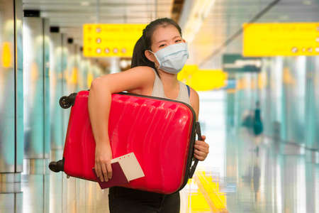 post covid19 new normal traveling - young happy and beautiful tourist Asian Korean woman in face mask with trolley suitcase at airport departures enjoying holiday travel after quarantine