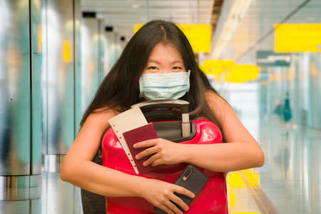 post covid19 new normal tourism - young happy and beautiful Asian Korean woman in face mask with trolley suitcase at airport departures enjoying holiday travel after quarantine