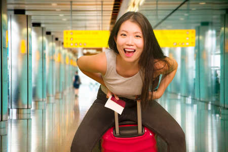 young beautiful and happy Asian girl traveling excited - Chinese tourist woman smiling cheerful with trolley suitcase at airport departures enjoying holiday travel in tourism concept