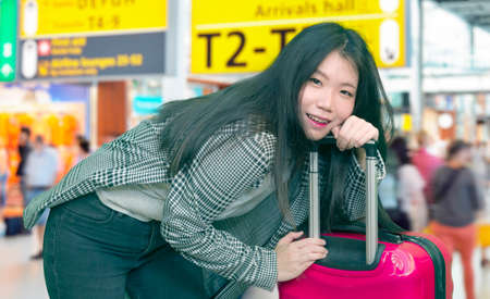 young Asian girl traveling happy and excited - young attractive and beautiful Korean woman with trolley suitcase at airport departures enjoying holiday travel smiling cheerful
