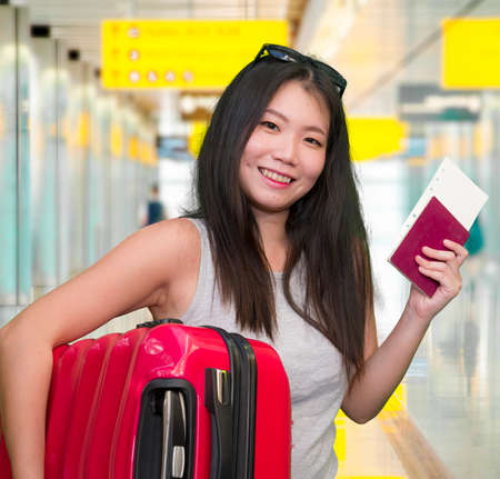 young beautiful and happy Asian girl traveling excited - Korean tourist woman smiling cheerful with trolley suitcase at airport departures enjoying holiday travel in tourism concept 写真素材