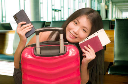 young beautiful and happy Asian Chinese tourist woman holding suitcase smiling cheerful and excited waiting at airport terminal departures in holidays travel concept 写真素材