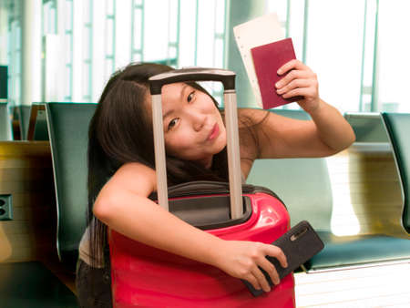 young beautiful and happy Asian Korean tourist woman holding suitcase smiling cheerful and excited waiting at airport terminal departures in holidays travel concept 写真素材
