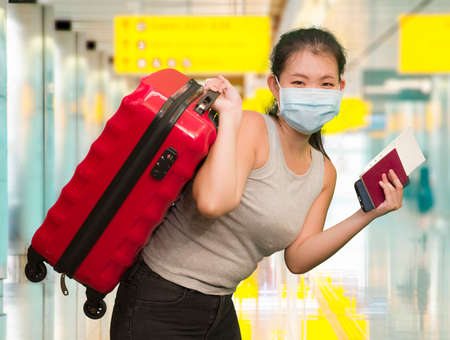 post covid19 new normal traveling - young happy and beautiful tourist Asian Chinese woman in face mask with trolley suitcase at airport departures enjoying holiday travel after quarantine