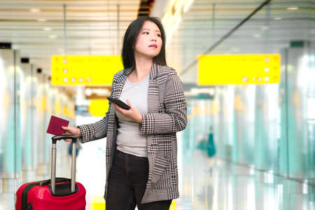young happy and beautiful Asian Chinese tourist woman holding suitcase smiling cheerful and excited at airport departures terminal in holidays travel concept
