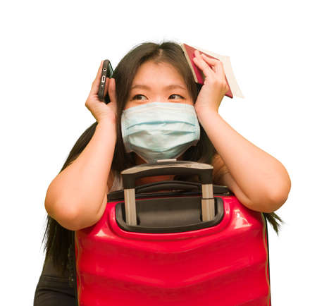 new normal traveling - young happy and beautiful Asian Korean woman in face mask carrying suitcase ready for enjoying holidays trip after covid19 quarantine 写真素材