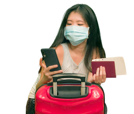 new normal traveling - young happy and beautiful Asian Korean woman in face mask carrying suitcase holding passport using mobile phone ready for holidays trip after covid lockdown