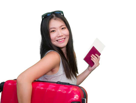young happy and beautiful Asian Korean woman carrying suitcase holding passport and boarding pass ready for holidays trip smiling cheerful and excited isolated on white background 写真素材