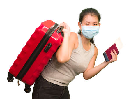 new normal traveling - young happy and beautiful Asian Japanese woman in face mask carrying suitcase ready for enjoying holidays trip after covid19 quarantine