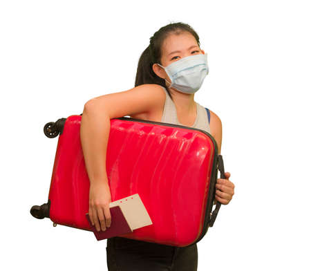 new normal traveling - young happy and beautiful Asian Chinese woman in face mask carrying suitcase ready for enjoying holidays trip after covid19 quarantine 写真素材