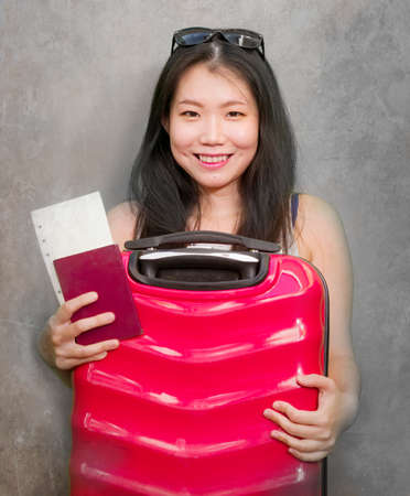 young happy and beautiful Asian Chinese woman carrying suitcase holding passport and boarding pass ready for holidays trip smiling cheerful and excited isolated on studio background