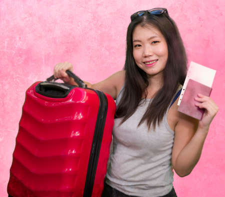young happy and beautiful Asian Korean woman carrying suitcase holding passport and boarding pass ready for holidays trip smiling cheerful and excited isolated on studio background