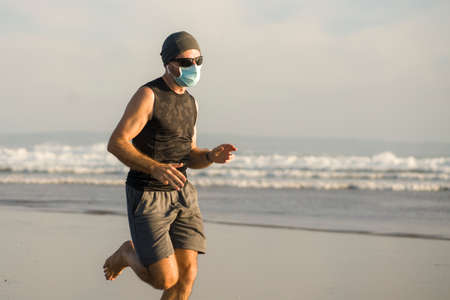 New normal beach jogging workout - young fit and attractive man in face mask running barefoot on sea training after covid19 lockdown feeling free outdoors in healthy lifestyle concept Standard-Bild