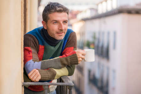 30s or 40s attractive and happy man at home balcony relaxed and cheerful enjoying cup of coffee looking to city street smiling and enjoying the urban view Stock fotó