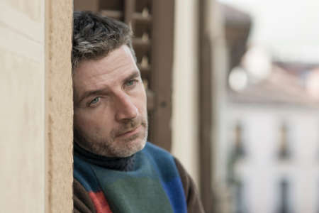 urban lifestyle emotional portrait of 40s handsome man sad and depressed at home balcony leaning upset feeling worried suffering depression problem looking to city street thoughtful