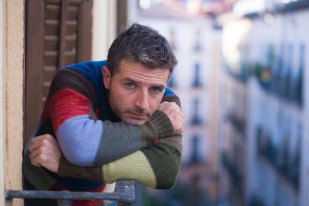 urban lifestyle emotional portrait of 30s handsome man sad and depressed at home balcony leaning upset feeling worried suffering depression problem looking to city street thoughtful