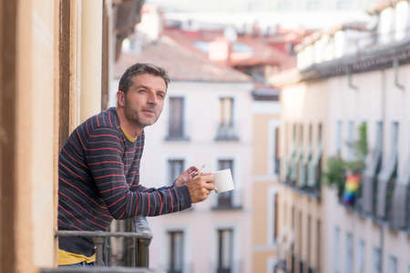 30s or 40s attractive and happy man at home balcony relaxed and cheerful enjoying cup of coffee smoking cigarette looking to city street smiling and enjoying the urban view