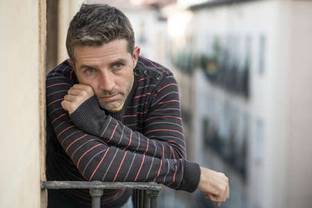 urban lifestyle emotional portrait of 30s handsome man sad and depressed at home balcony leaning upset feeling desperate suffering depression problem looking to city street thoughtful